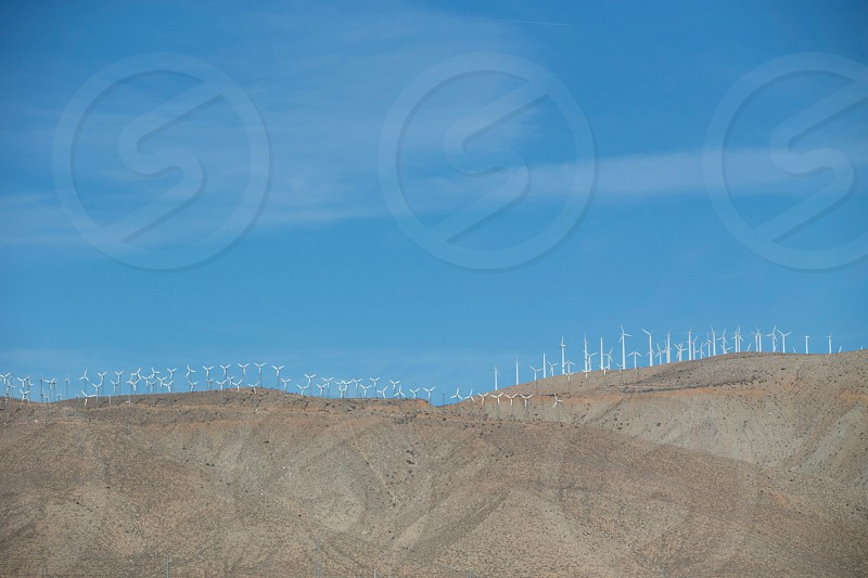 white metal wind mills in a row photo