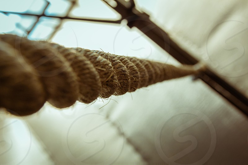 Brown climbing rope hanging from roof - Close up view from below