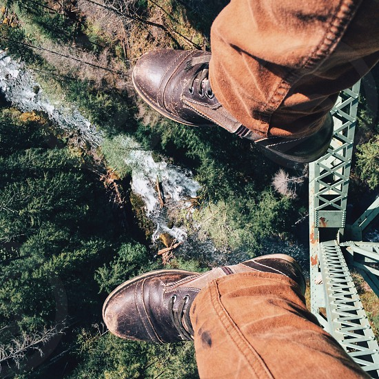 men's khaki and and brown leather boots hanging over the edge of a bridge photo