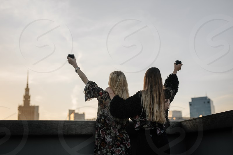 Two gitls stand on the rooftop and have a drink photo