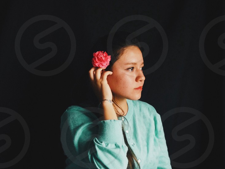 woman with black hair wearing blue blouse and pink flower on hair photo