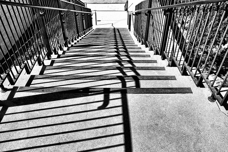 Black and white image - looking down a long  cement staircase with angular shadows photo