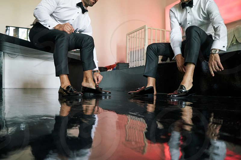 The man is wearing slip-on black glossy shoes to prepare for the wedding ceremony black wooden floor - closed up low angle photo
