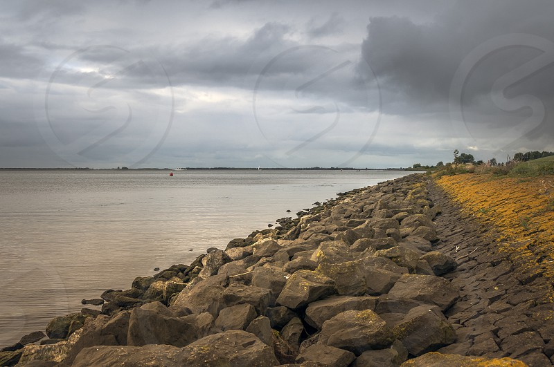 dutch coastline with rocks for dike protection and dark clouds during bads weather photo