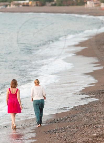 2 women walking near seashore during daytime photo