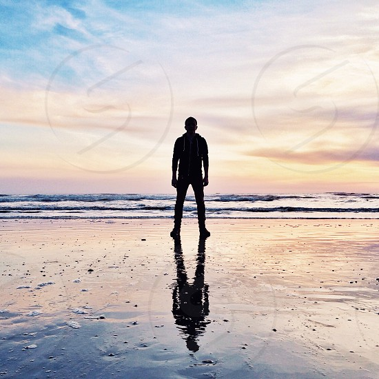 human silhouette standing on sea shore photo