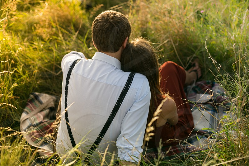 couples sitting on grass field photo