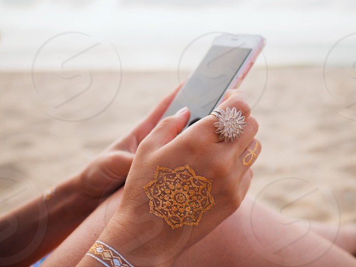 Woman with smartphone on sea beach. Hands of young girl with flash tattoo and bohemian boho rings using mobile device. Technology concept. photo