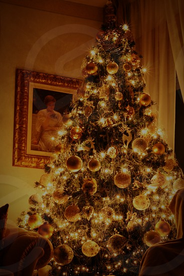green Christmas tree with orange and white baubles decor photo