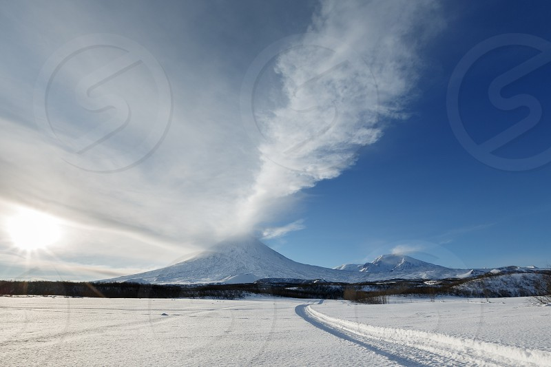 Beautiful volcanic landscape of Kamchatka Peninsula: wintry view of eruption active Klyuchevskoy Volcano (Klyuchevskaya Sopka) - ejection from crater of volcano plume of gas steam and ashes. Eurasia Far East Russia Kamchatsky Krai. photo