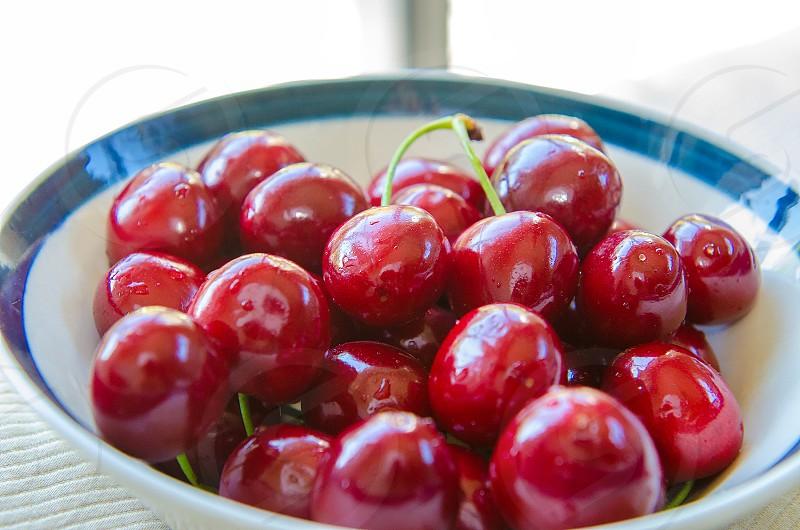 red cherries on white blue ceramic bowl photo