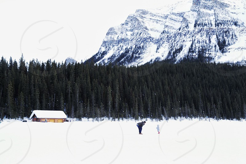 man and child standing on snow covered land near house surrounded with green leafed tree near mountain during daytime photo