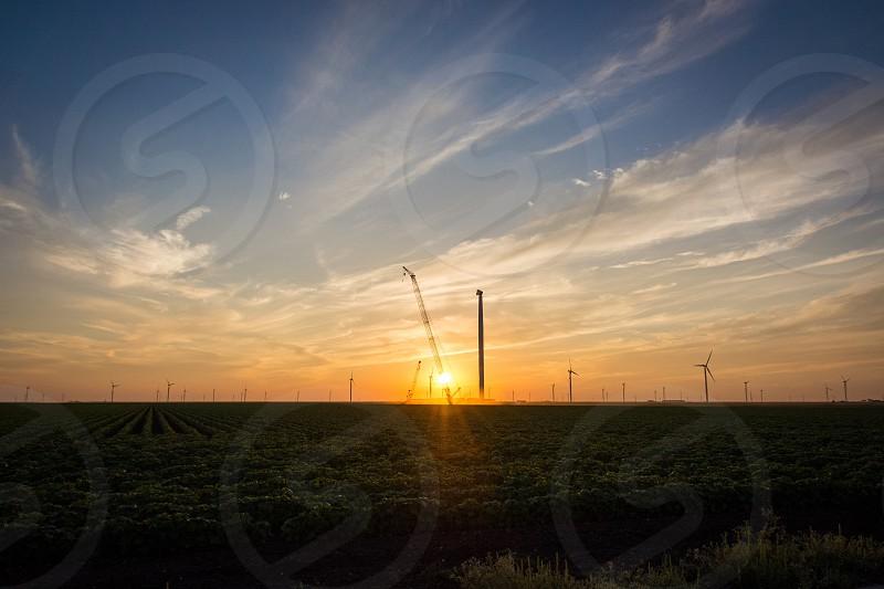 Crane heavy construction field sun orange windmill wind mill turbine  photo