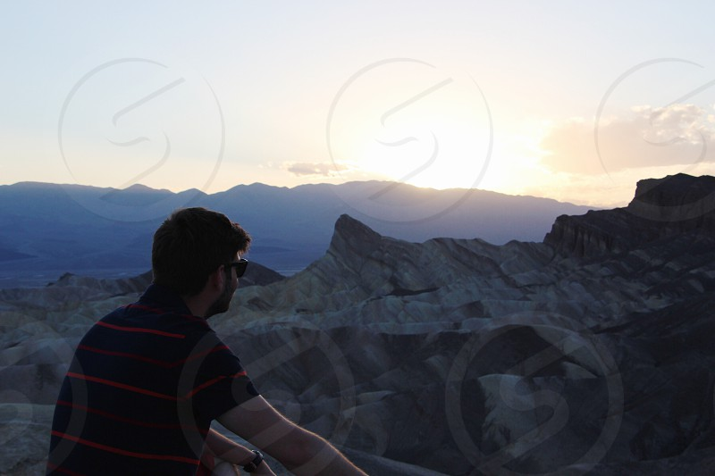 man in black red striped polo shirt facing the mountain photo