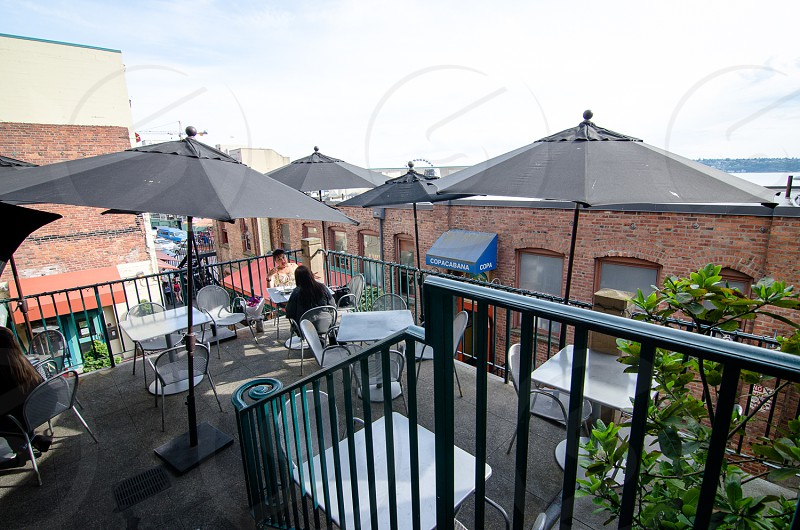 two people sitting on chair under parasol on roof top photo