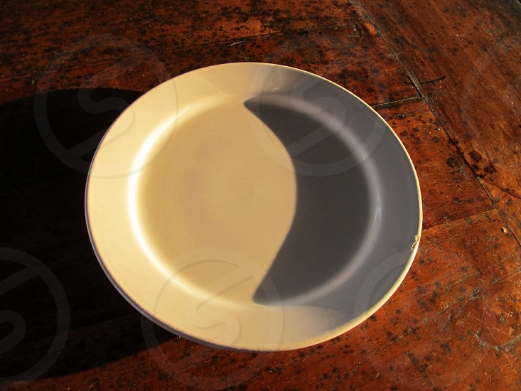 Empty white plate on wood background with shadows photo