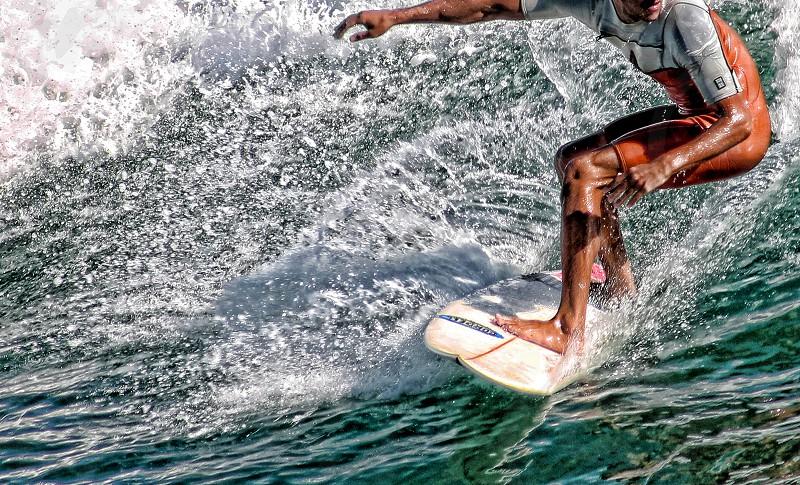 A surfer balances on a surfboard riding a foamy wave photo