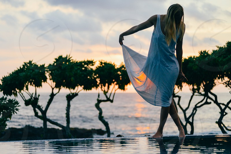 woman in white dress facing down near pool side during sunset photo