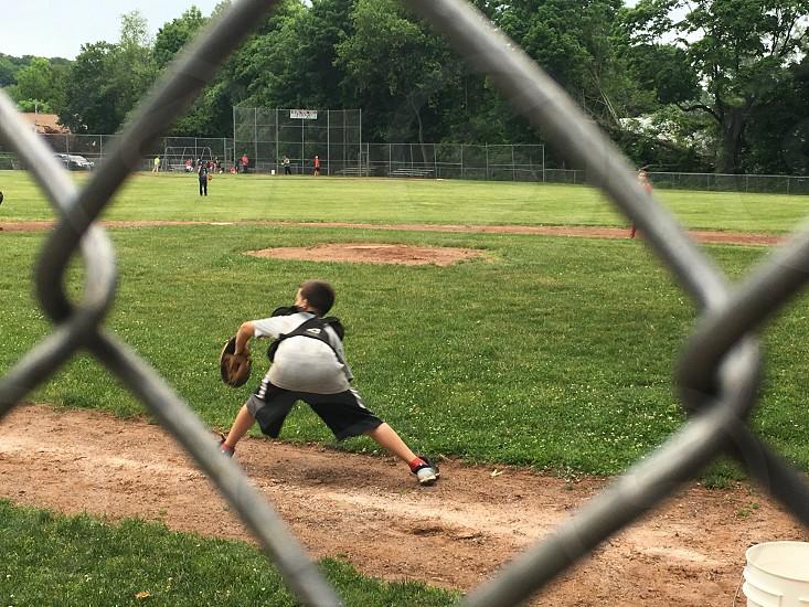 boy wearing baseball mitt standing on baseball ground field during daytime photo