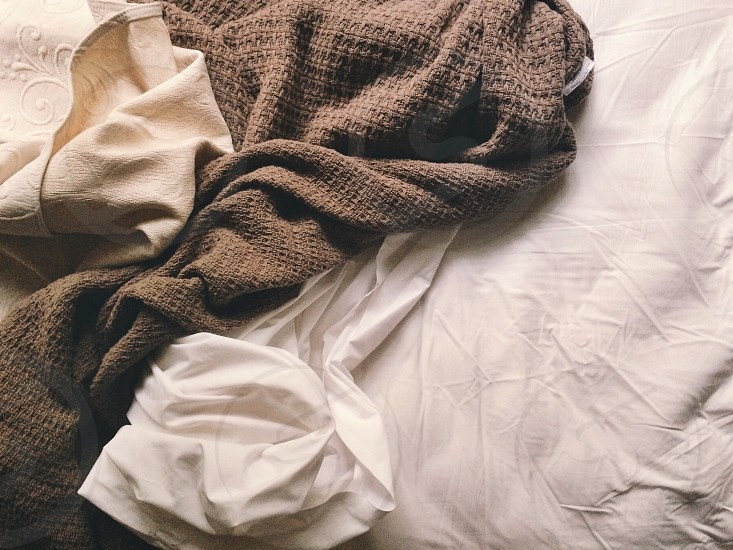 a moody picture of a rumpled bed with neutral colored sheets and blankets photo