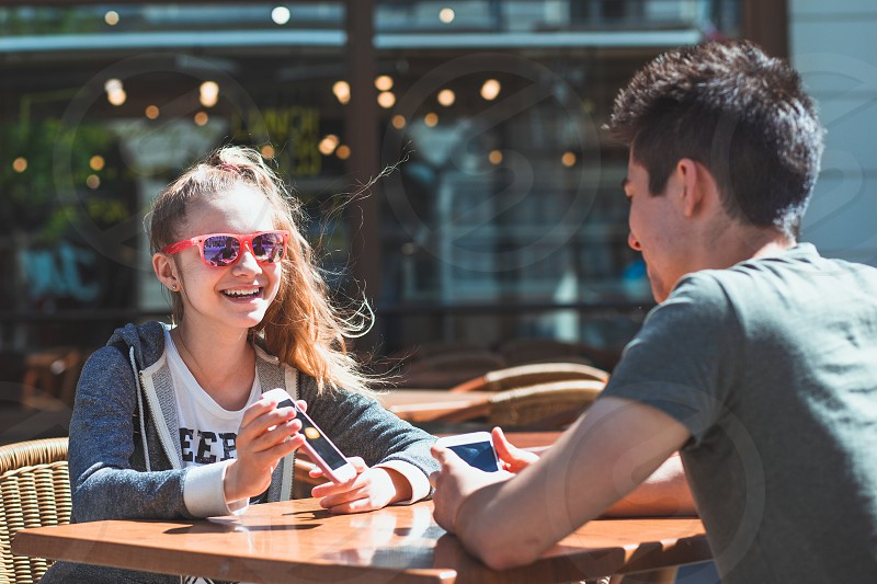 Young woman and man sitting in pavement cafe a the table talking and using mobile phones photo
