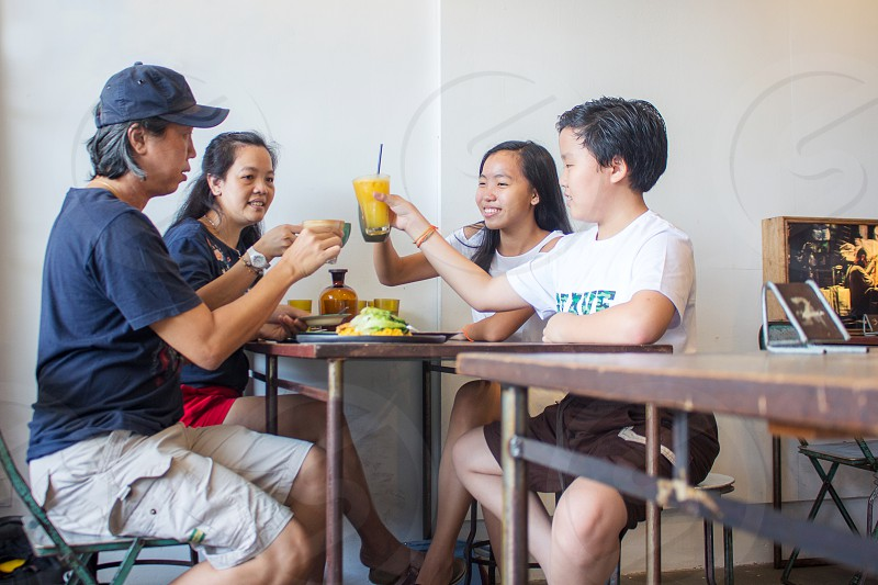Chinese ethnic family having meal together and toss for celebration  happy mood photo