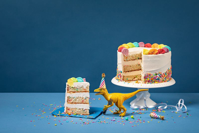 Hungry toy dinosaur wearing a hat and holding a fork next to a birthday Cake on a Blue background photo