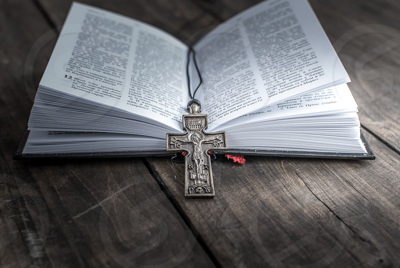 Closeup of  Christian cross necklace lying on an open page of the bible. photo
