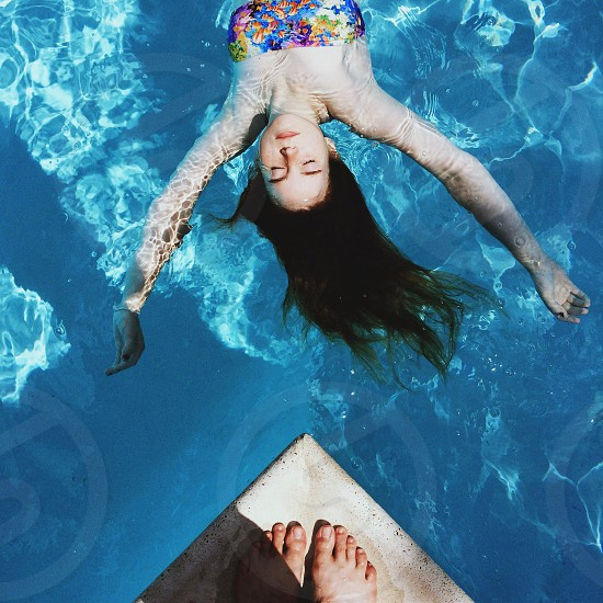 woman wearing a floral bandeau swimsuit floating in a pool photo