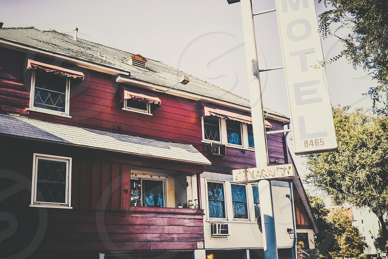Motel burgundyvibrant exterior sign city town slum Windows abandoned photo