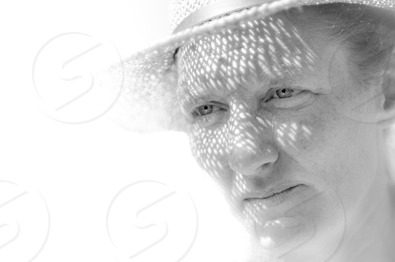 Shadow from straw hat falling on face photo
