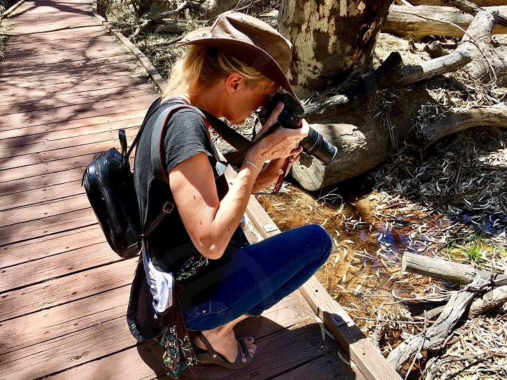 Creatives workplace workspace woman female photographer outback Australian outback Flinders bush wildlife photography camera equipment backpack Australian hat photographing shooting nature outdoors crouching getting the shot focusing aiming professional blonde  photo