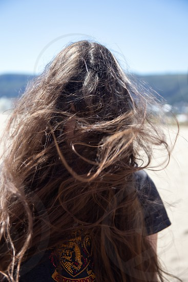 Portrait of brunette girl with long flying hair in the wind outdoors. Young casual woman with wavy hair covering her face. Teenage girl with messy windy tousy blowsy hair. photo