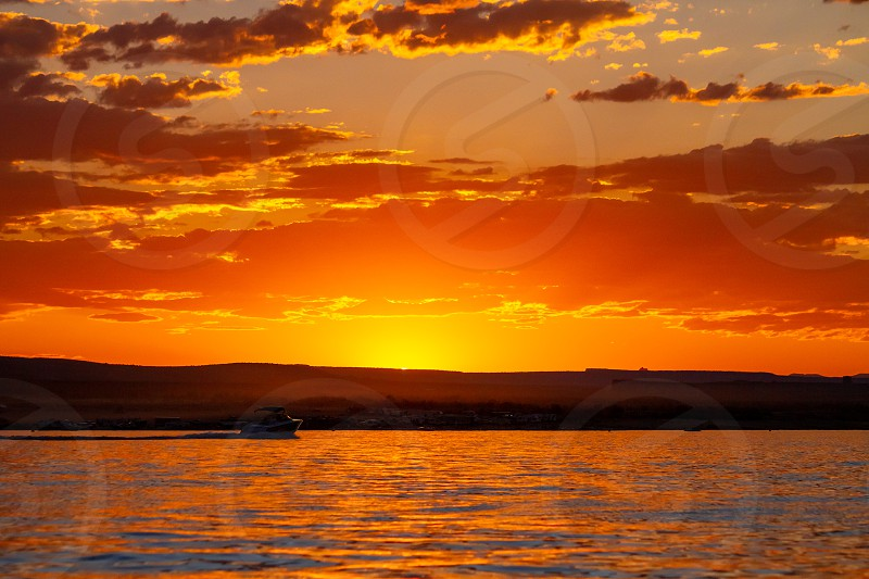 A lone speed boat races towards the setting sun on Lake Powell in Arizona in Wahweap Bay.  The sky and water are glowing orange during golden hour and dust glows on the horizon from a dirt road. photo