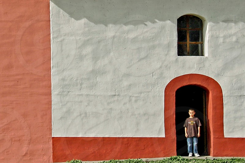 Boy framed in arched door of an adobe building photo