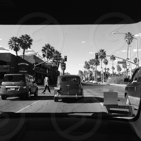 gray scale photography of woman walking on road near cars photo