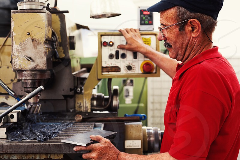 Worker in big industrial company producing parts on his machine.  photo