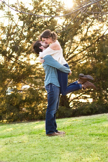 man carrying a woman while kissing in the middle of green grass field photo