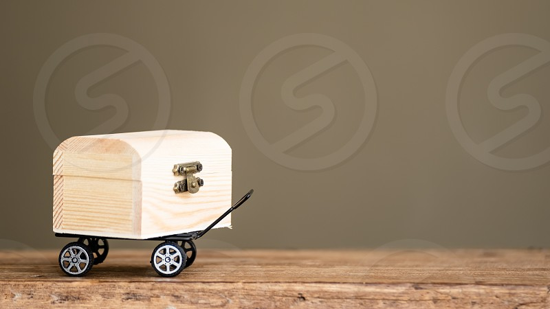 goods in treasure chest delivery on black toy wagon copy space photo