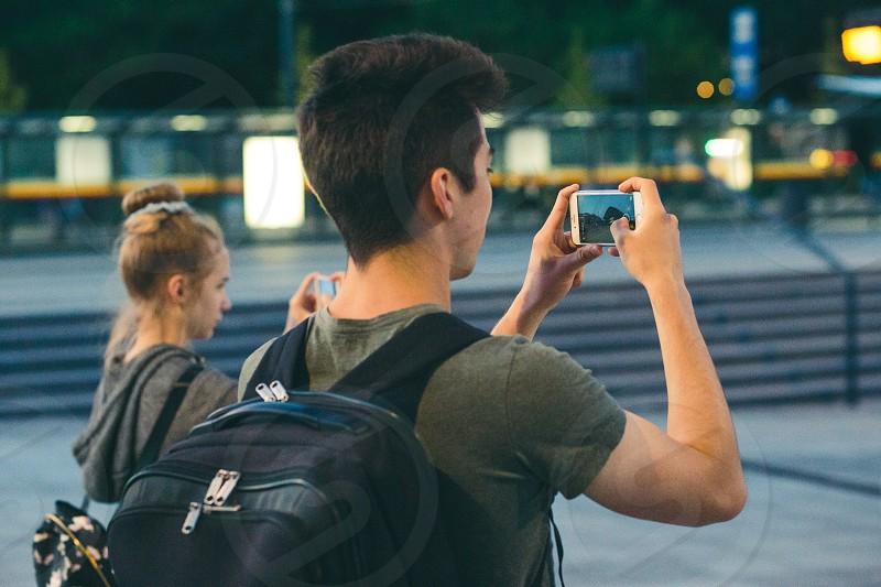 Young people taking photos using a smartphones in the city at night photo