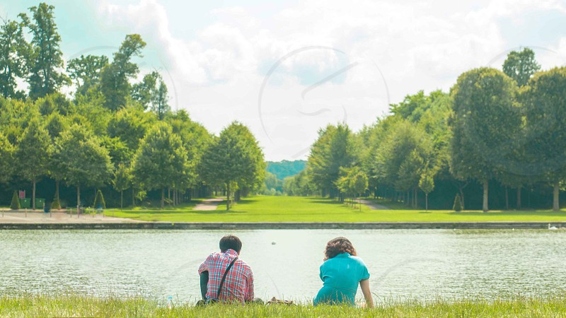 man and woman sitting on grass near river over sunrise view photo