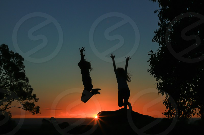 Girls jumping sunset photo