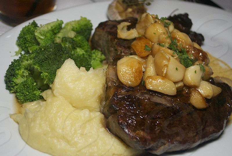 beef steak sauted with garlic and broccoli dish served on white ceramic plate photo