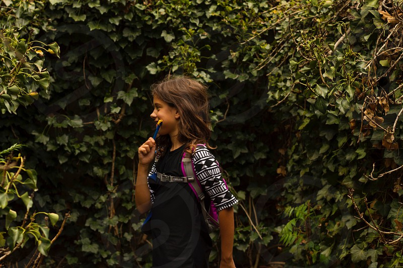 female child wearing white and black elbow sleeve shirt and pink backpack surrounded by plants photo