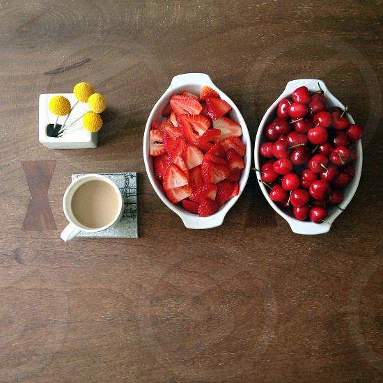 sliced strawberries whole cherries in bowl near coffee in mug on table photo