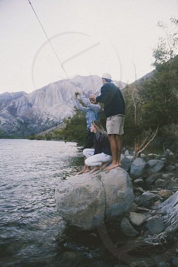 man child and woman fishing from rock photo