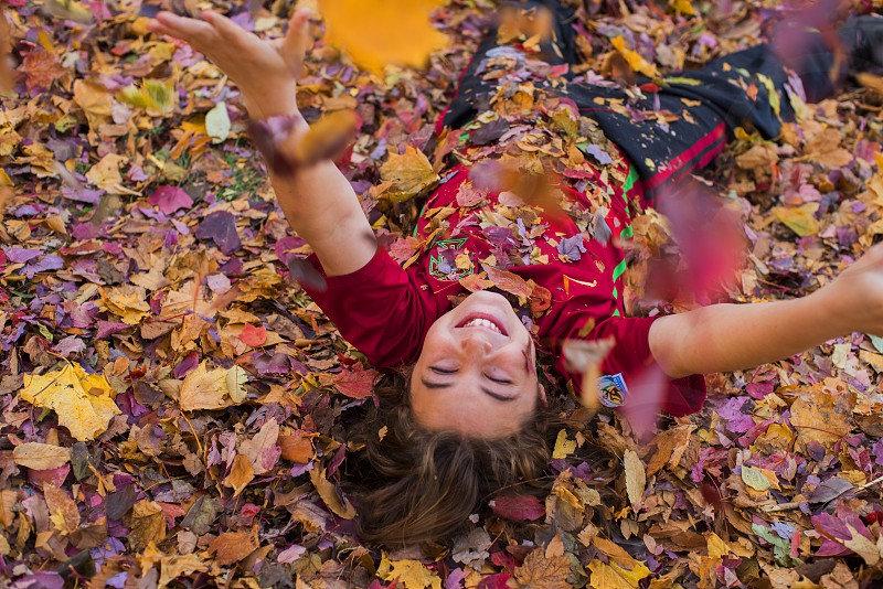 girl in red t shirt lying on ground surrounded with leaves during daytime photo