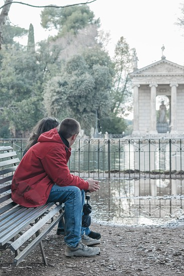 Two people watch the lake. Photo taken at the lake of Villa Borghese Rome. photo