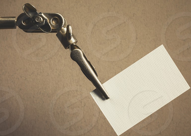 Metal clamp holds white clean paper suitable for textual message or title.  photo