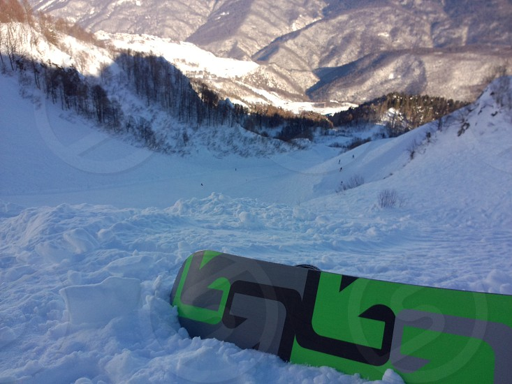 green black and gray snowboard on snow photo